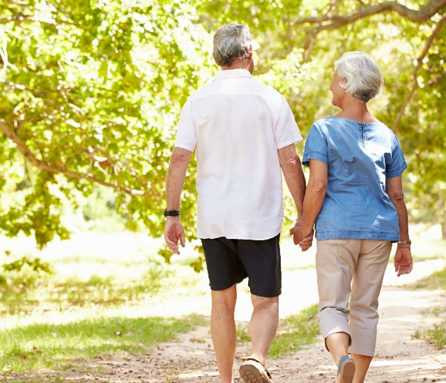 Photo of an older couple walking together down a leafy path